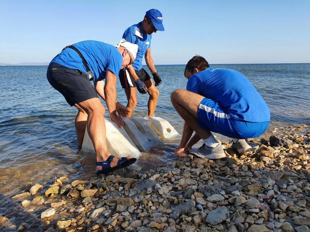 Raccolta di un rifiuto ingombrante dalla spiaggia di Is Pruinis